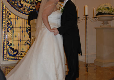 Kathleen's daughter and son-in-law on their wedding day kissing at the ceremony